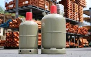 5 kg und 11 kg Gasflasche im Lager mit roten Gasflaschen