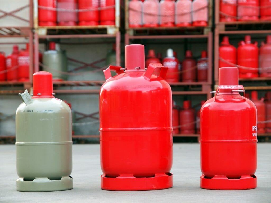 Rote und graue Gasflaschen in Lager vor Regalen
