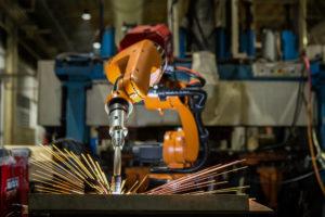 Orangener Laser Roboter schweißt Werkstück unter Funken